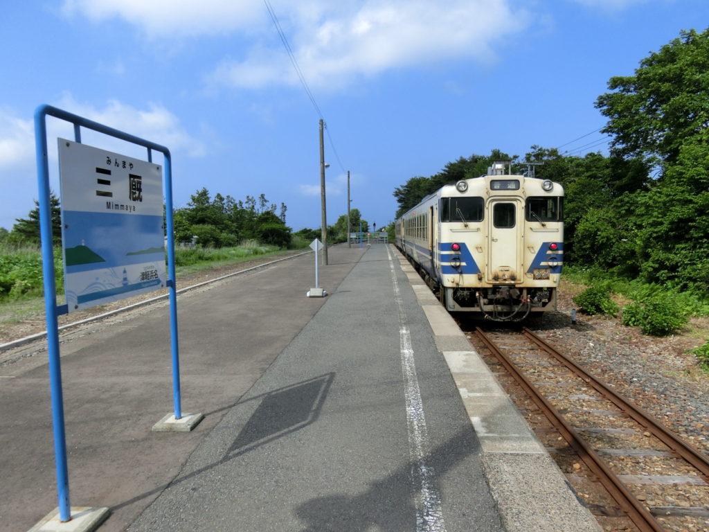津軽線・三厩駅ホームに停車中のキハ40系気動車と駅名標